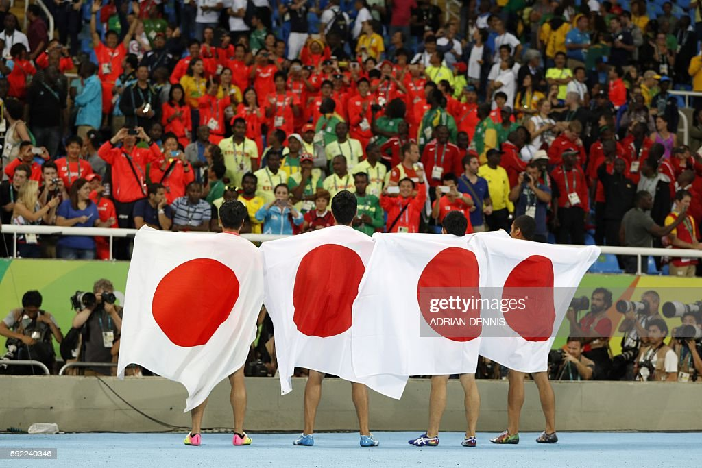 TOPSHOT - Team Japan celebrates after finishing second of the Men's 4x100m Relay Final during the athletics event at the Rio 2016 Olympic Games at the Olympic Stadium in Rio de Janeiro on August 19, 2016. / AFP / Adrian DENNIS