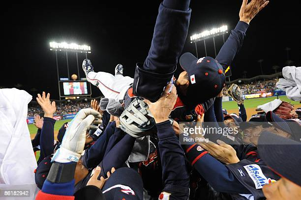 Team Japan celebrates by tossing manager Tatsunori Hara into the air after defeating Korea during the World Baseball Classic final game at Dodger...