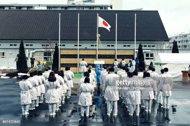 Team Japan members watch the national flag is hoisted during the welcome ceremony at the Athletes Village ahead of the Nagano Winter Olympic Games on...