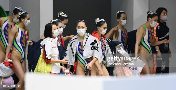 Team Japan members wearing face masks leave the pool after competing in the Team Technical Routine on day one of the Artistic Swimming Japan...