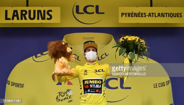 Team Jumbo rider Slovenia's Primoz Roglic celebrates his overall leader yellow jersey on the podium at the end of the 9th stage of the 107th edition...