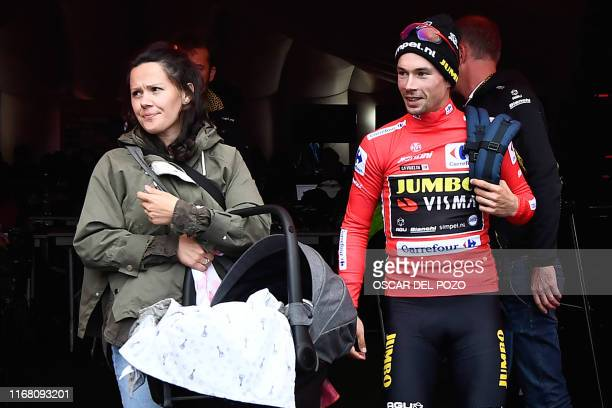 Team Jumbo rider Slovenia's Primoz Roglic wearing the leader's red jersey leaves the press room with his wife Lora Klinc carrying their child after...
