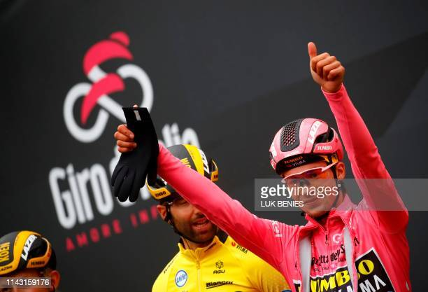 Team Jumbo rider Slovenia's Primoz Roglic wearing the overall leader's pink jersey gestures as he takes the start of the second stage of the 2019...