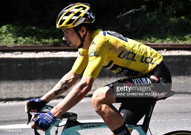 Team Jumbo rider Slovenia's Primoz Roglic wearing the overall leader's yellow jersey rides after a crash during the fourth stage of the 72nd edition...