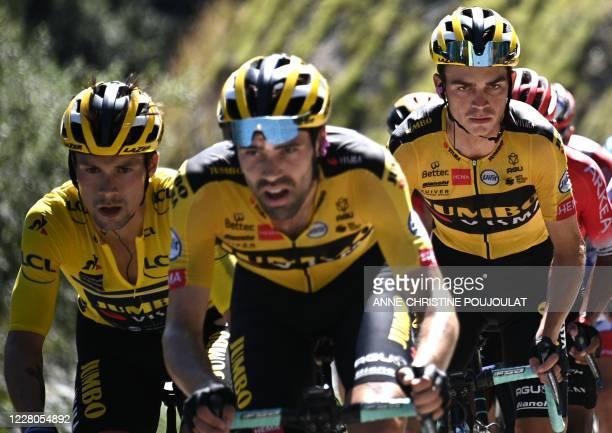 Team Jumbo rider Slovenia's Primoz Roglic wearing the overall leader's yellow jersey climb flanked by his teammate Team Jumbo rider US Sepp Kuss...