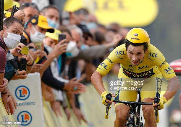 Team Jumbo rider Slovenia's Primoz Roglic wearing the overall leader's yellow jersey crosses the finish line at the end of the 20th stage of the...