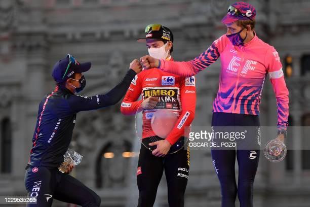 Team Jumbo's Slovenian winner Primoz Roglic celebrates on the podium with Team Ineos' Ecuadorian second-placed rider Richard Carapaz and EF Pro...
