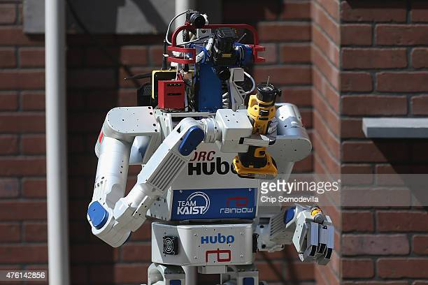 Team Kaist's DRCHUBO robot successfully uses a power hand tool during its successful final run in the Defense Advanced Research Projects Agency...
