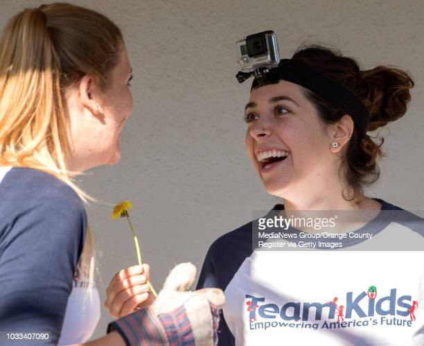 Team Kids volunteer Molly Hudash left and Francesca Apollonio a Team Kids Youth Council coach share a laugh over a dandelion flower as the group...