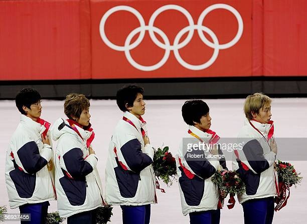 Team Korea listens to the Korean national anthem on the medal stand after winning the gold medal in the men's 5000 meter relay in Short Track Speed...