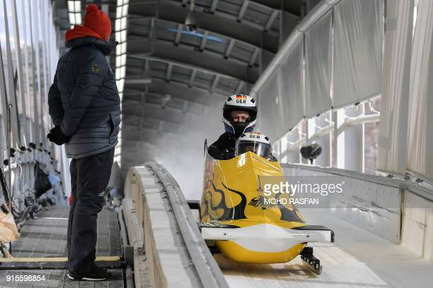Team leader and driver Anna Koehler of Germany brakes at the finishing line during the second unofficial bobsleigh women's training session at the...