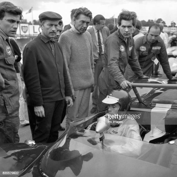 Team Lotus boss Colin Chapman left with flat cap has a glum expression to match that of new Grand Prix World Champion Jim Clark on the grid at Brands...