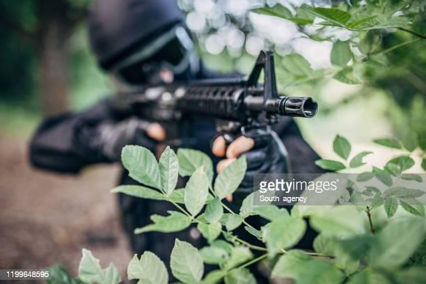 swat team man with machine gun hiding in wilderness - metralhadora imagens e fotografias de stock