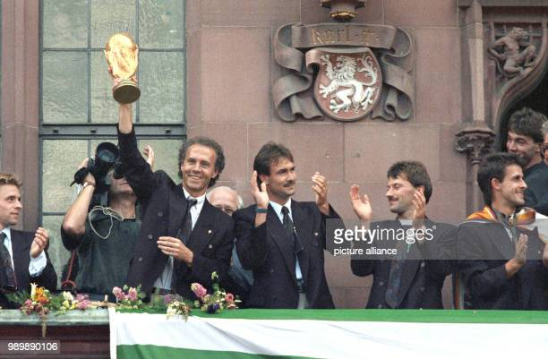 Team manager Franz Beckenbauer is holding up the World Cup trophy on the balcony of Frankfurt's town hall the Roemer Raimond Aumann Guenther Hermann...