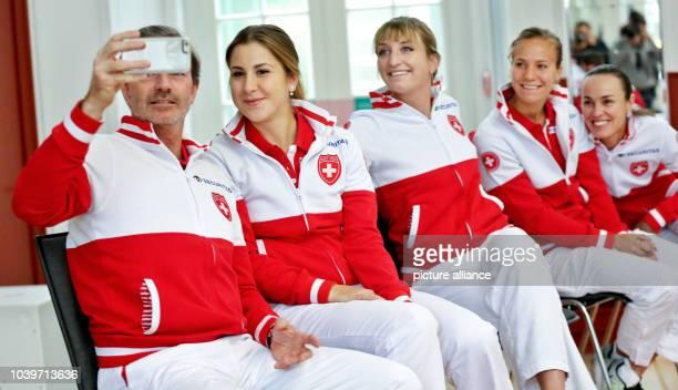 Team manager Heinz Guenthardt takes a selfie with Swiss tennis players Belinda Bencic Timea Bacsinszky Viktorija Golubic and Martina Hingis following...