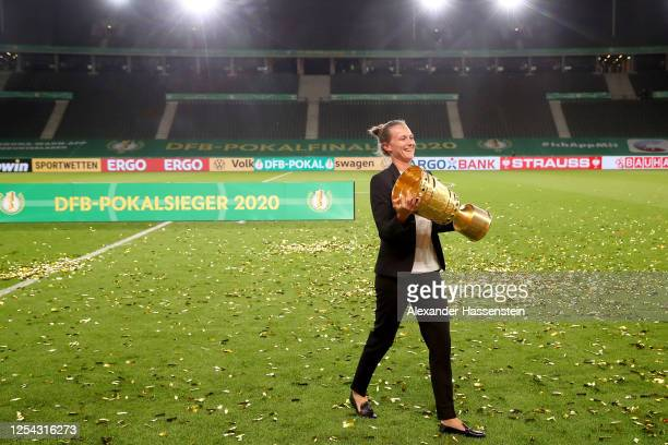 Team manager Kathleen Krueger of FC Bayern Muenchen poses with the trophy in celebration after the DFB Cup final match between Bayer 04 Leverkusen...
