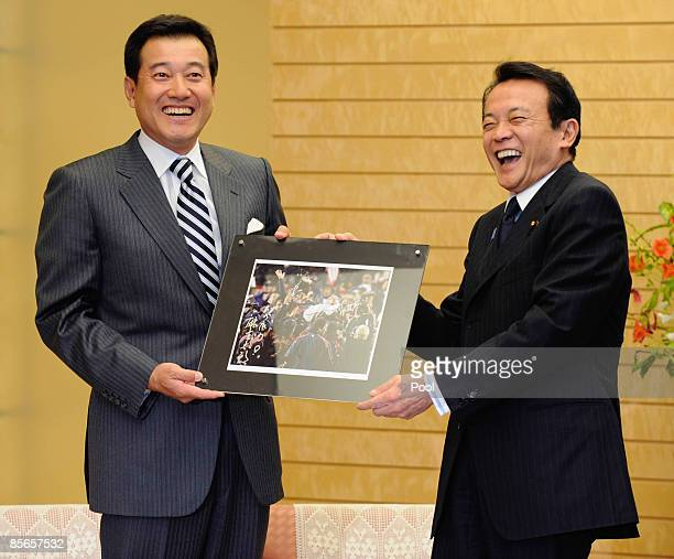 Team manager of Japan's World Baseball Classic squad Tatsunori Hara presents a memorial photograph of Hara to Japanese Prime Minister Taro Aso at...
