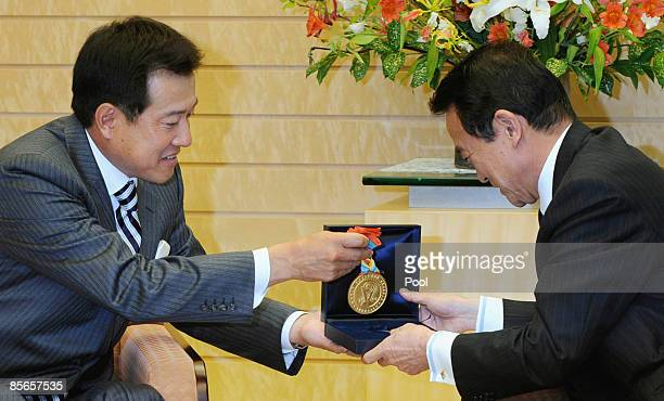 Team manager of Japan's World Baseball Classic squad Tatsunori Hara displays a gold medal for winning the WBC championship to Japanese Prime Minister...