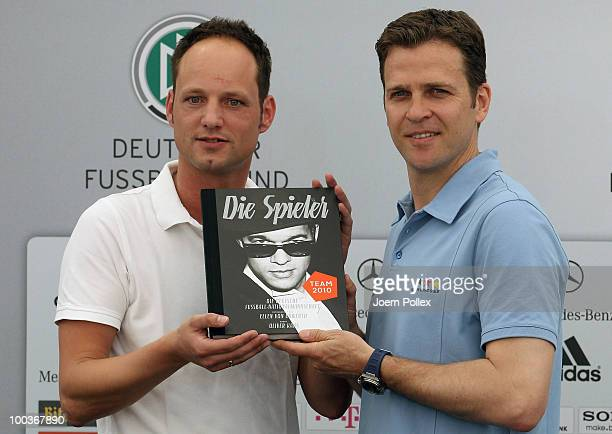 Team manager Oliver Bierhoff of Germany and Stephan Braun of DFB are pictured with the illustrated book Die Spieler during a press conference at...