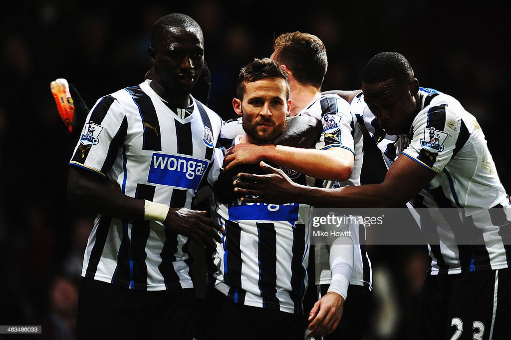 A team mate holds a bottle as Yohan Cabaye (C) of Newcastle United is congratulated by team mates after scoring his sides third goal during the Barclays Premier League match between West Ham United and Newcastle United at the Boleyn Ground on January 18, 2014 in London, England.