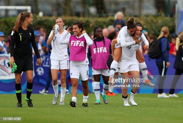 A team mate jumps on the back of Amelie Delabre of France as they celebrate after the FIFA U20 Women's World Cup France 2018 group A match between...