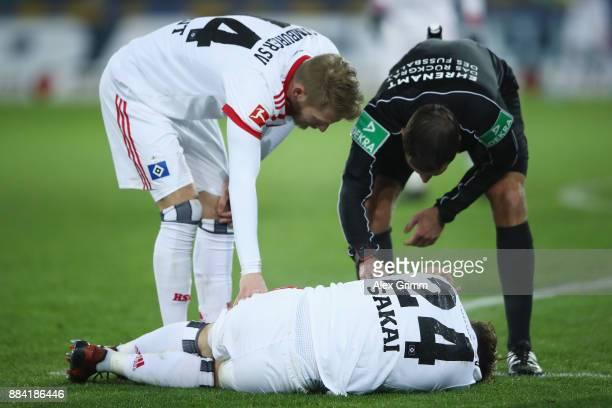 Team mates Aaron Hunt and goalkeeper Christian Mathenia of Hamburg look after Gotoku Sakai during the Bundesliga match between SportClub Freiburg and...