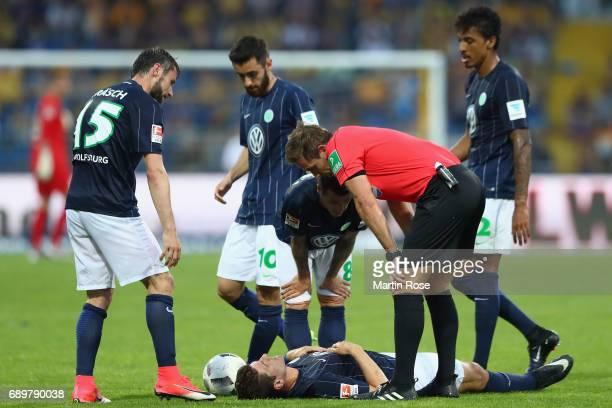 Team mates and referee Tobias Stieler look after Mario Gomez of Wolfsburg during the Bundesliga Playoff leg 2 match between Eintracht Braunschweig...
