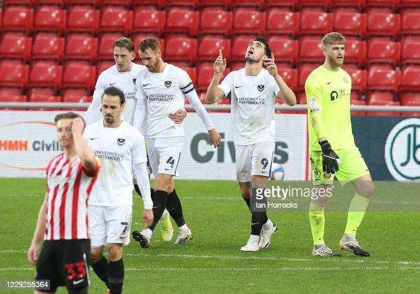 Team mates celebrate with John Marquis of Portsmouth after he scores the third goal for his side from the penalty spot during the Sky Bet League One...