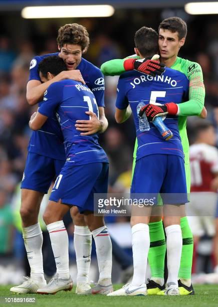 Team mates Marcos Alonso and Pedro embrace alongside Kepa Arrizabalaga and Jorginho of Chelsea following the Premier League match between Chelsea FC...