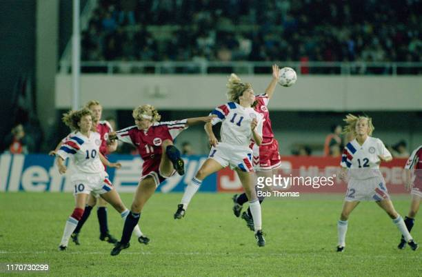 Team mates Michelle Akers and Carin Jennings look on as Julie Foudy of the United States leaps with Catherine Zaborowski of Norway for the ball...