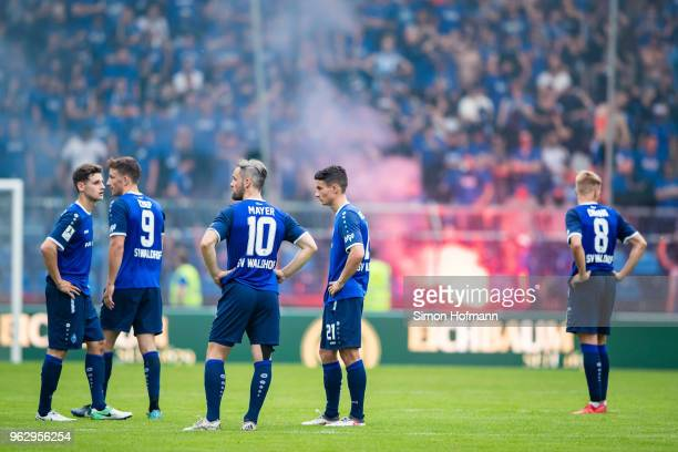Team mates of Mannheim react as their supporters light fireworks during the Third League Playoff Leg 2 match between SV Waldhof Mannheim and KFC...