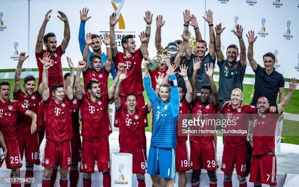 Team mates of Muenchen celebrate with the trophy after winning the DFL Supercup match between Eintracht Frankfurt and Bayern Muenchen at...