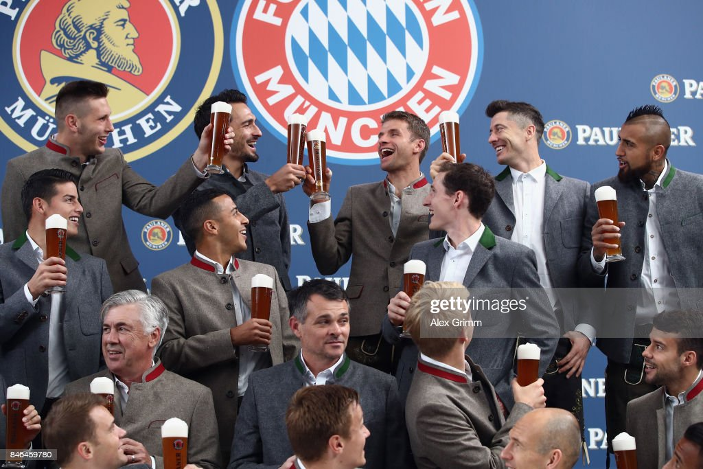 Team mates raise a birthday toast to Thomas Mueller during the FC Bayern Muenchen Paulaner photo shoot in traditional Bavarian lederhosen on September 13, 2017 in Munich, Germany.