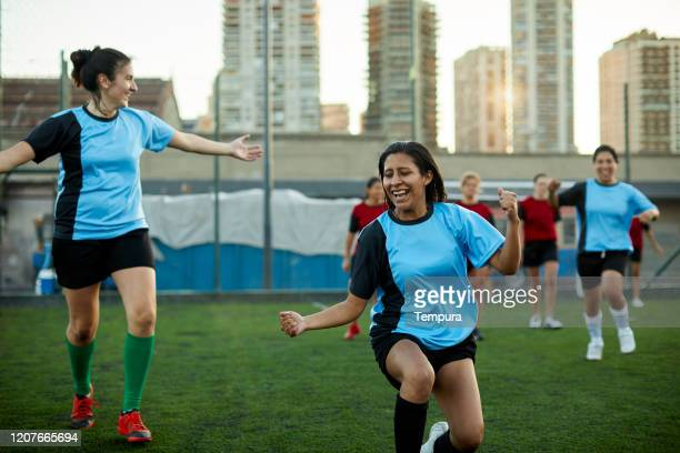team mates run celebrating scoring a goal during a match. - soccer competition stock pictures, royalty-free photos & images