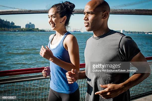 Team mates running along waterfront, New York, USA