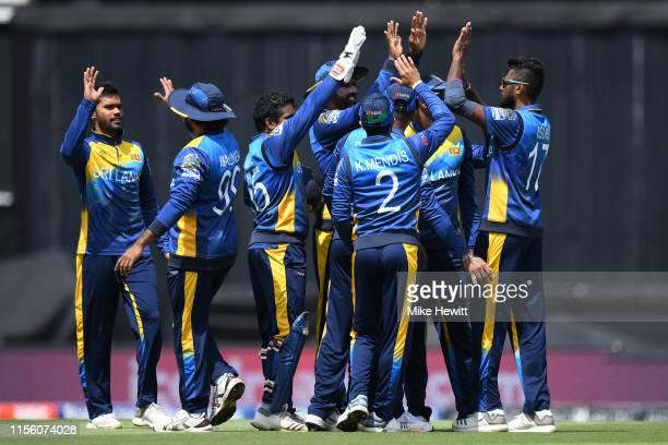 Team mates rush to congratulate Isuru Udana of Sri Lanka for catching Usman Khawaja of Australia off the bowling of Dhananjaya de Silva during the...