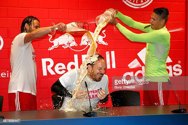 Team mates Timo Roettger and Daniel Frahn showers head coach Alexander Zorniger of Leipzig with beer during the press conference to celebrate...