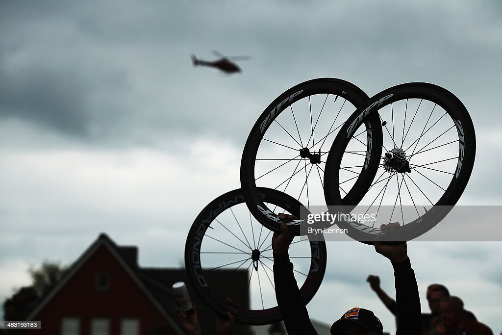 Team mechanics hold spare wheels in the air for passing riders during the 98th Tour of Flanders from Bruges to Oudenaarde on April 6, 2014 in Oudenaarde, Belgium.