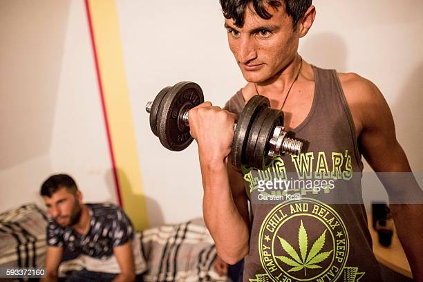 Team member Esmatulla Sayid Ataf from Jalalabad in Afghanistan shows his fitness with a dumbbell during a team discussion with other members lead by...