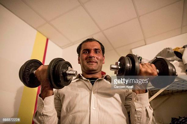 Team member Imran Ali from Garjat from Pakistan shows his fitness with a dumbbell during a team discussion with other members lead by pakistani team...