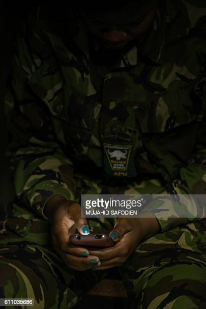 A team member looks at her phone as female members of the antipoaching team Black Mamba prepare for the night patroles on September 24 2016 in the...