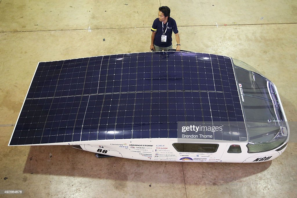 A team member of the #88 Kogakuin University Solar Vehicle Project waits with his car during scrutineering for the 2015 Bridgestone World Solar Challenge at Darwin Showgrounds on October 14, 2015 in Darwin, Australia.