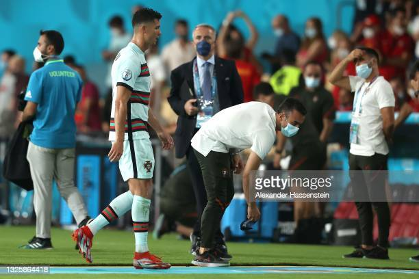 Team member picks up Cristiano Ronaldo's captain's armbands as he leaves the pitch following defeat in the UEFA Euro 2020 Championship Round of 16...