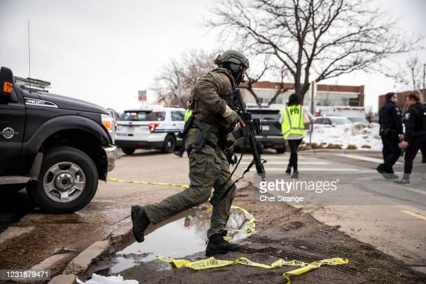 Team member runs toward a King Soopers grocery store where a gunman opened fire on March 22, 2021 in Boulder, Colorado. Dozens of police responded to...