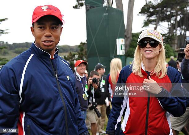 US team member Tiger Woods and his wife Elin Nordegren wait for the rest of the team to finish play after Woods sunk his putt on the 13th green to...