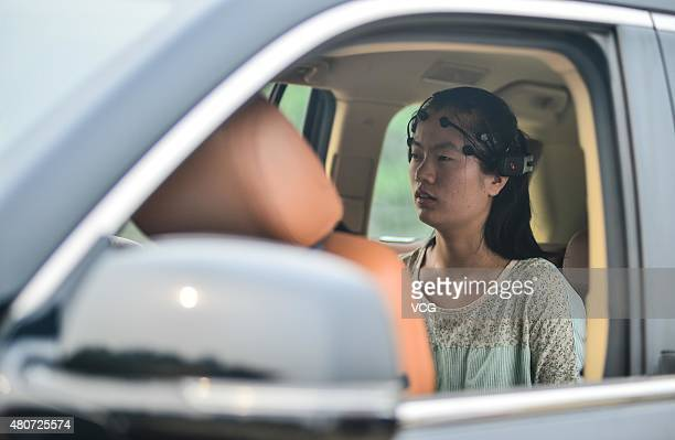 A team member wearing an electroencephalograph acquisition equipment orders a mindcontrolled car to go forward at Nankai University on July 15 2015...