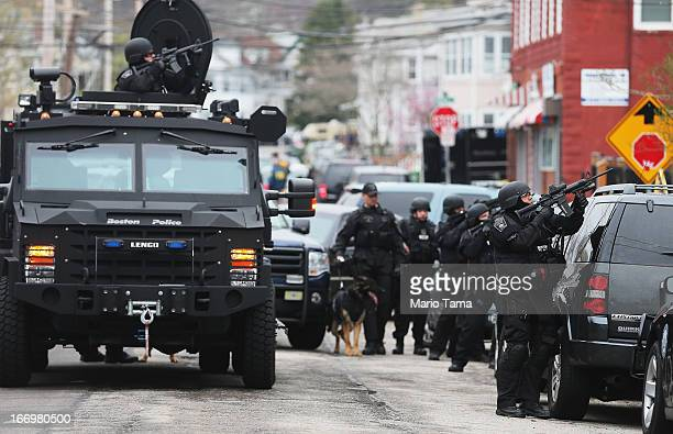 SWAT team members aim their guns as they search for one remaining suspect at an apartment building on April 19 2013 in Watertown Massachusetts...