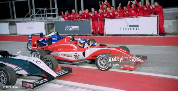 フィニッシュラインでドライバーを応援するチームメンバー - レーシングドライバー ストックフォトと画像