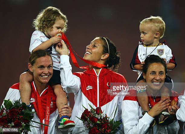 USA team members Christie Rampone Carli Lloyd Kate Markgraf and children pose on the podium with their Gold medals after the Women's Football on Day...