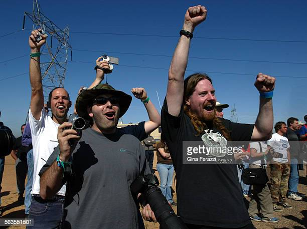 Team members from The Golem Group Mike Radfordleft Josh Arensberg and David Caldwell cheer as their autonomous vehicle passes the mile 4 marker to...